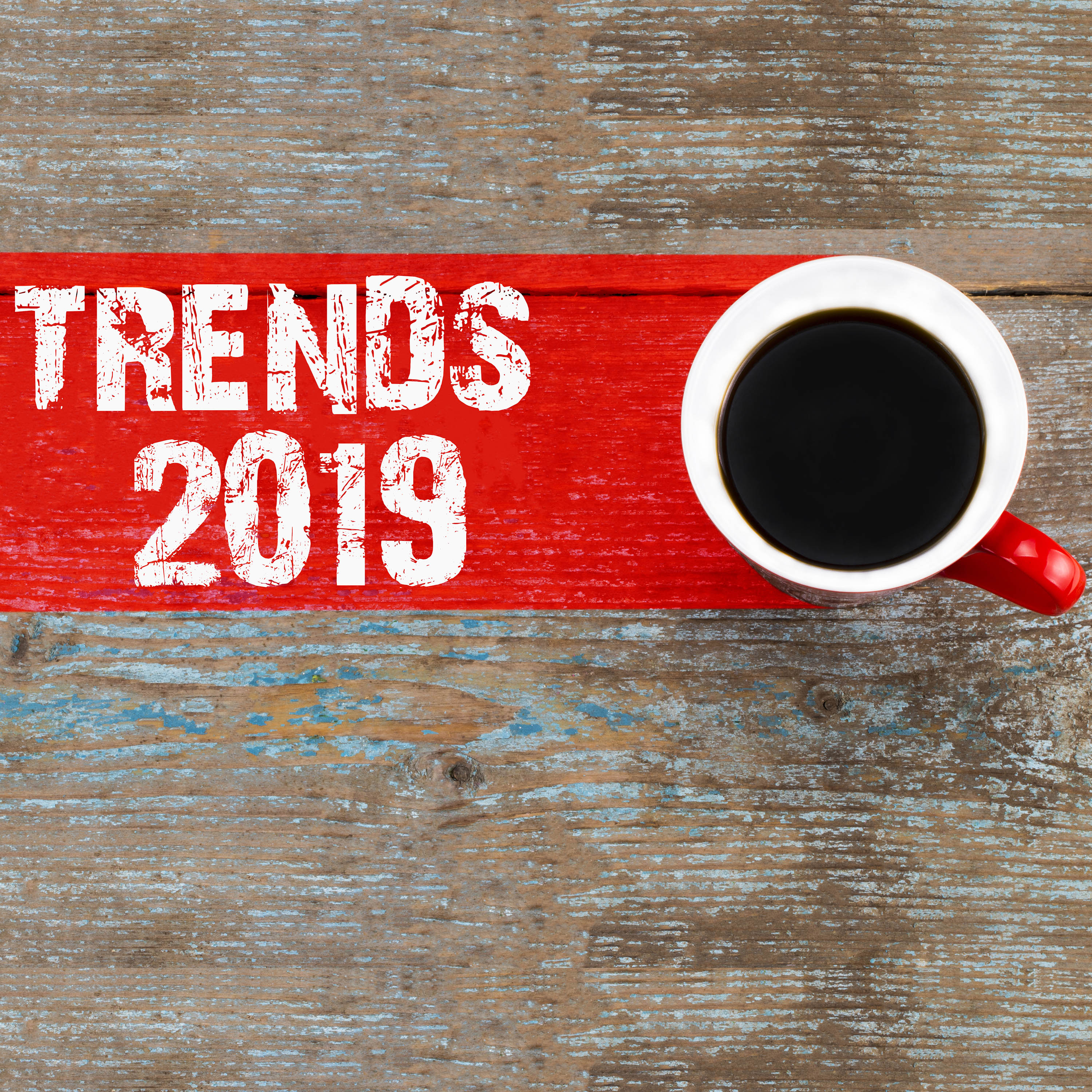 Trends 2019 / Cup of coffee with trends inscription on wooden ba
