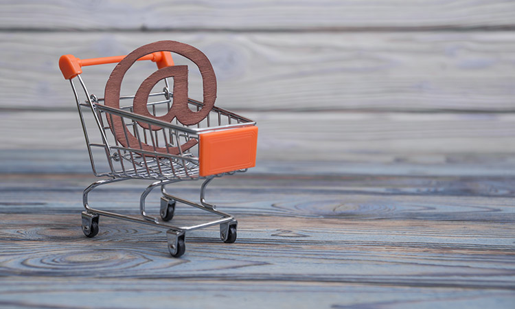 an email symbol, shopping cart on a wood board background. The i